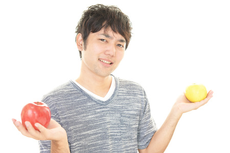 collate: Smiling Asian man with apples Stock Photo