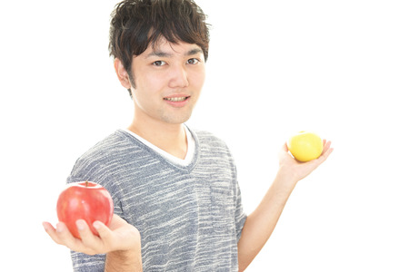 calibrate: Smiling Asian man with apples Stock Photo