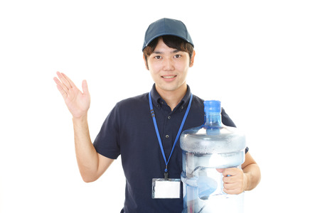 man drinking water: Worker with a container of water