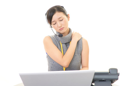 emotional pain: Tired call center operator who has a shoulder pain