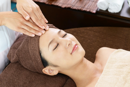 facial: Woman getting a facial massage Stock Photo