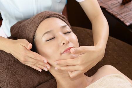 Die Frau, die sich um ihr Gesicht nimmt