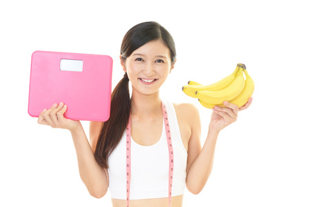 Smiling young woman with banana Lizenzfreie Bilder