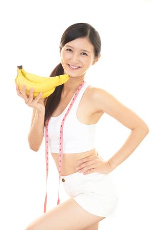 バナナを持つ若い女性を笑顔 写真素材