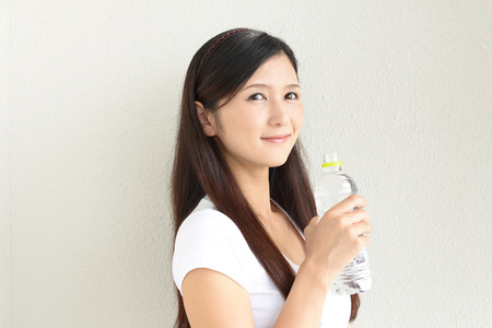 The young woman drinking a bottle of water