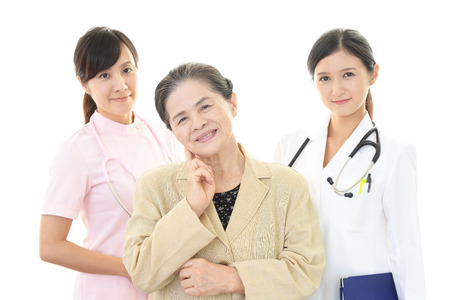 Hospital care: Smiling medical stuff and an old lady Stock Photo