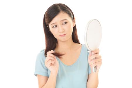 De vrouw kijkt ongelukkig met haar haren