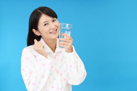 refrescar: The young woman drinking a glass of water