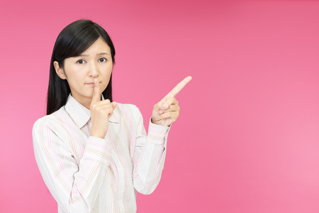 talkative: Portrait of a woman making silence gesture Stock Photo
