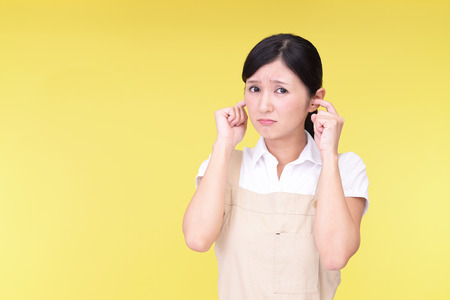 bother: Woman who holds her ears Stock Photo