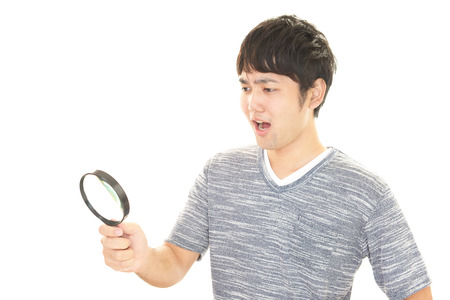 magnifying glass man: Surprised Asian man with a Magnifying glass