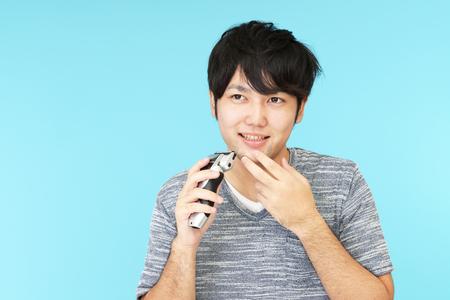 electric razor: A man shaving with electric razor