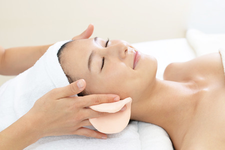 esthetician: Beautiful young woman receiving facial massage