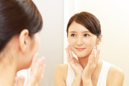 Asian woman looking at her face in mirror 스톡 콘텐츠