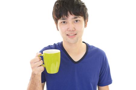 hombre tomando cafe: Caf� de consumici�n del hombre asi�tico.