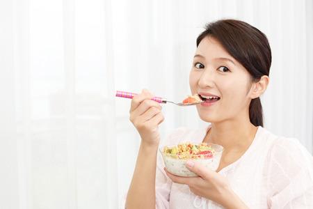 comiendo cereal: Mujer que come alimentos saludables
