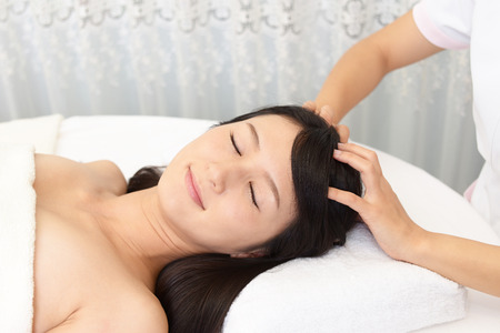 receives: Woman in spa salon receives head massage