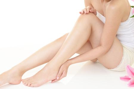 Frau, die sich um ihre Beine dauert