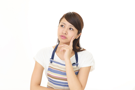 Uneasy Asian housewife Stock Photo
