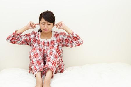 Vrouw die haar oren houdt Stockfoto