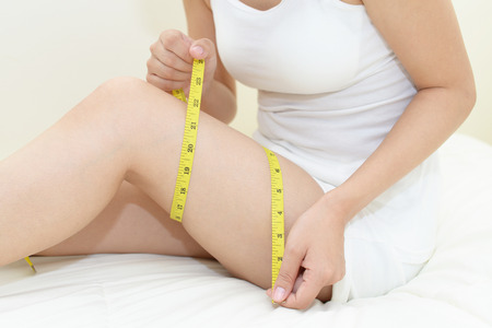 Woman who is measuring her thigh Stock Photo