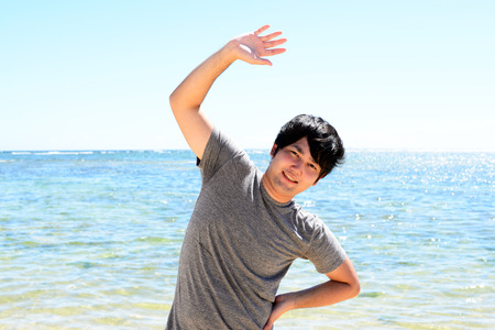 Smiling Asian man on the beach