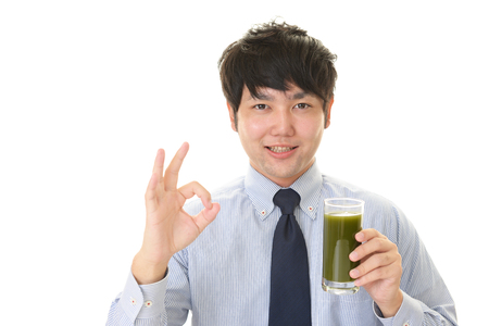 Asian man drinking a glass of vegetable juice