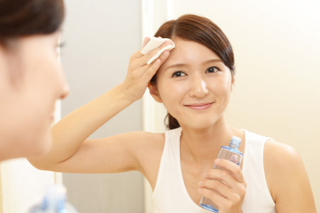 Asian woman looking at her face in mirror Stock Photo