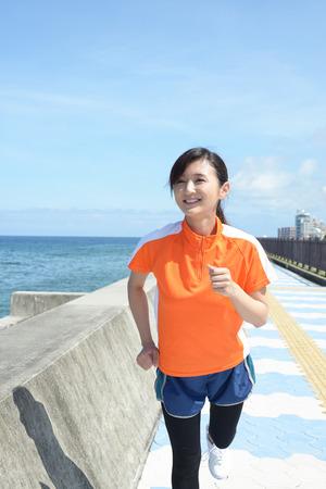 Jonge vrouw joggen bij de zee
