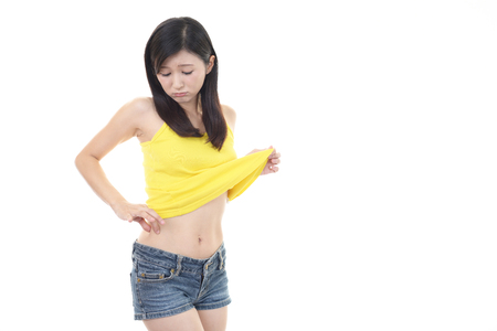 uneasy: Woman checking fat on her belly Stock Photo