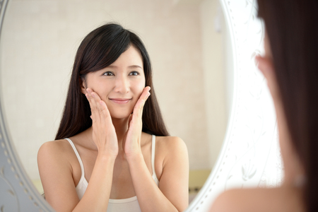 Asian woman looking at her face in mirror Standard-Bild