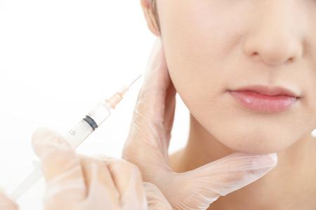 Joven mujer recibe inyección de belleza en su cara