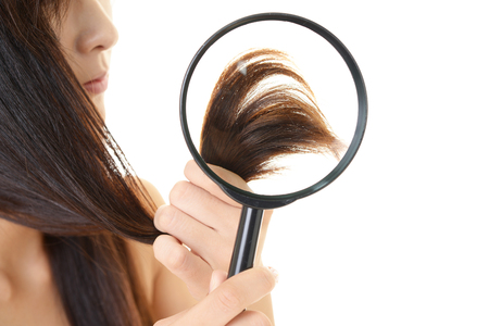 Woman looks at the tops of her hair