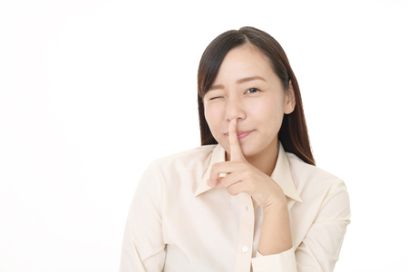 Woman placing finger on lips. Stock Photo