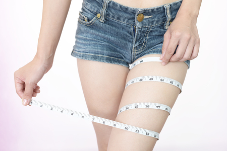 Woman who is measuring her thigh Imagens