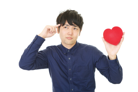 heartbreak issues: Depressed Asian man with a red heart Stock Photo