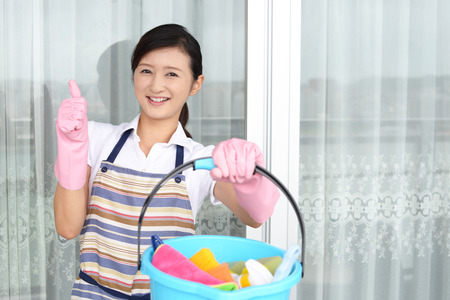 Smiling woman posing with cleaning supplies Stock Photo