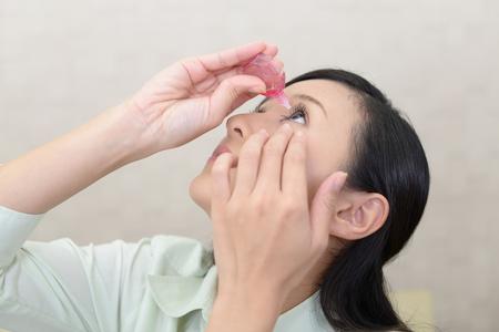 Woman who puts eye drops in her eyes 版權商用圖片