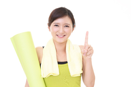 Beautiful woman with a yoga mat at the gym Stock Photo