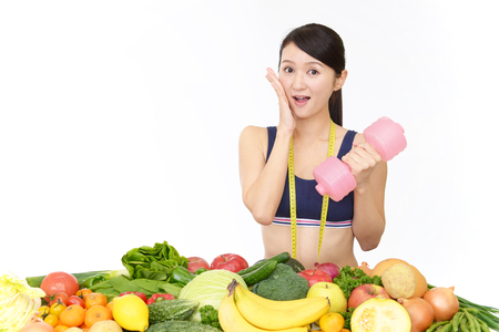 Beautiful slim woman with dumbbell and vegetables Stock Photo