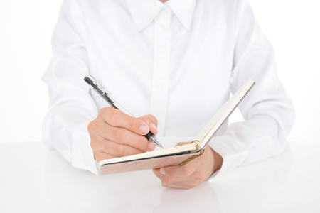 Woman is writing notes and planning her schedule