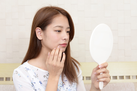 woman mirror: Asian woman looking at her face in mirror Stock Photo