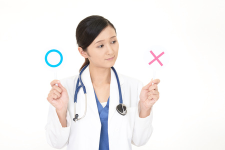 Asiatischer Arzt mit einem Ja oder Nein-Zeichen