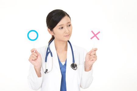 médecin asiatique asiatique avec un oui ou aucun signe