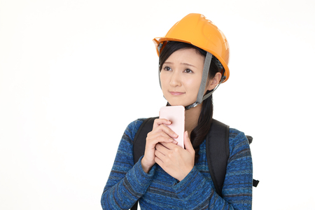 countermeasures: Uneasy Asian woman with a safety hat Stock Photo