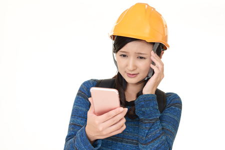 Uneasy Asian woman with a safety hat Stock Photo