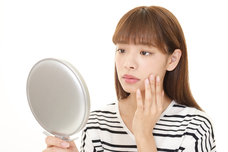 salon background: Young woman having skin problems Stock Photo