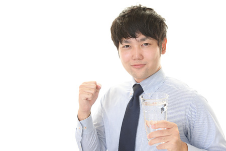man drinking water: Portrait of a man holding a glass of water