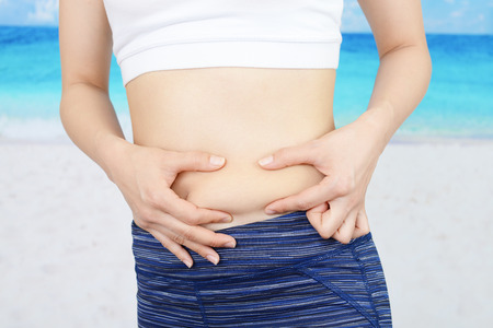 tired: Close up portrait of woman checking fat on her belly