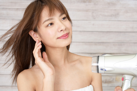 Young woman blow drying her hair Stock Photo